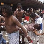 Hurricane Katrina victims rush dehydrated elderly woman to medics after she loses consciousness.